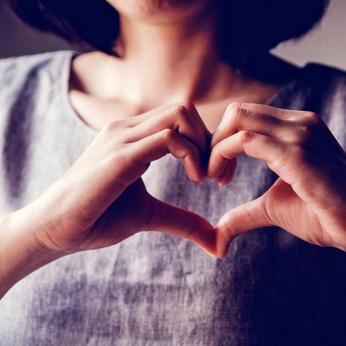 Woman holding heart hands